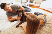 Young couple on bed with pet dog — Stock Photo