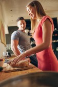 Young couple in kitchen preparing food — Stock Photo