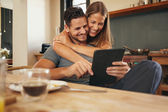 Loving young couple catching up on social media smiling — Stock Photo