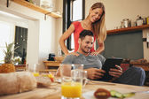 Beautiful couple in kitchen and using a touchpad — Stock Photo