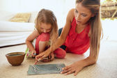 Mother and little daughter together drawing pictures — Stock Photo