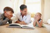 Young man with two kids reading a story book — Stock Photo