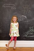 Innocent little girl standing with chalk drawings at home — Stock Photo