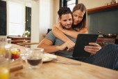 Young couple in the kitchen catching up on morning updates — Stock Photo