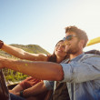 Woman taking selfie on road trip with man — Stock Photo #74125823