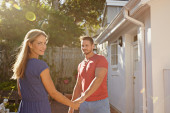 Beautiful young couple outside their house — Stock Photo