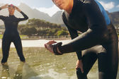 Athletes in wet suits preparing for triathlon competition — Stock Photo