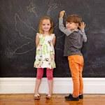 Two little kids in front of blackboard with angel wings — Stock Photo #75511649