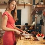 Beautiful woman preparing breakfast in her kitchen — Stock Photo #75512521