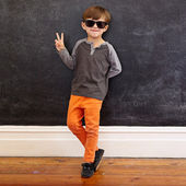Cool little boy gesturing victory sign — Stock Photo