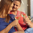 Smiling young couple celebrating with wine — Stock Photo #76791635