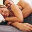 Cute young couple in love lying on bed — Stock Photo #76819539