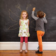 Little girl in front of a blackboard with boy drawing angel wing — Stock Photo #77263272