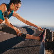 Female runner stretching before running — Stock Photo #77264116