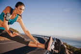 Woman stretching her legs before a run — Stock Photo