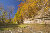 Fall Colors and a Limestone Cliff over a Quiet Stream. — Stock Photo