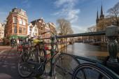 Amsterdam, niederlande - 19. märz 2014: bunte häuser am kanal in sonnigen frühlingstag. fahrräder stehen auf der brücke geparkt — Stockfoto