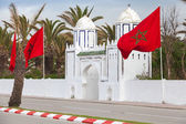 Ancient white gate to the park and flags in Tangier, Morocco — Stock Photo