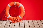 Lifebuoy stands on wooden floor nearby red wall of lifeguard station — Stock Photo