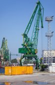 Yellow metal cargo container and green crane stand in port — Stock Photo