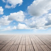 Brown wooden floor with perspective and cloudy sky — Stockfoto