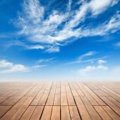 Коричневый деревянный пол с перспективой и яркие облачное небо — Стоковое фото