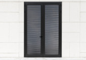 Black metal door in white wall with tiling — Stock Photo