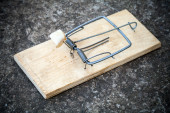 Old mousetrap with fat bait stands on concrete floor — Stock Photo