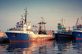 Industrial fishing boats are moored in port. Vintage toned photo — Stock Photo