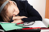 Blond Caucasian schoolgirl sleeps on the desk in school — Stock Photo