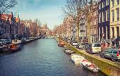AMSTERDAM, NETHERLANDS - MARCH 19, 2014: Canal perspective in spring sunny day. Ordinary people walk on coasts — Stock Photo