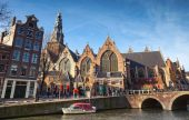 AMSTERDAM, NETHERLANDS - MARCH 19, 2014: Oude Kerk. Old church on canal coast in Amsterdam. Ordinary people walk on the street — Stock Photo