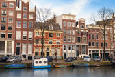 Amsterdam, nederländerna - 19 mars 2014: färgglada hus längs kanalen banvallen i vårdag. vanliga människor är vid kusten — Stockfoto