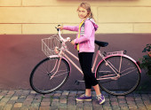 Little blond Caucasian girl in pink with bicycle, vintage toned  — Stock Photo