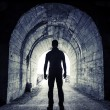 Young man stands in dark tunnel and looks in the glowing end — Stock Photo #53689593