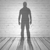 Shadow of a man on white brick wall and wooden floor — Stock Photo