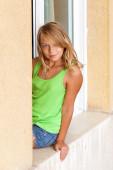 Little blond Caucasian girl in the window, outdoor portrait — Stock Photo