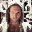 Young man in hood, street artist portrait with grungy graffiti — Stock Photo #54062343