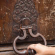 Hand and old rusted knocker on brown wooden door in Paris, Franc — Stock Photo #54667121