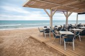 Sea side bar interior with wooden floor and metal armchairs — Stock Photo