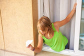 Little blond Caucasian girl with paper plane in the window — Stock Photo