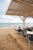 Sea side bar interior with wooden floor and metal armchair — Stock Photo