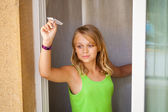 Little blond Caucasian girl with small paper plane in window — Stock Photo