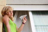 Little blond Caucasian girl with paper plane in window — Stock Photo