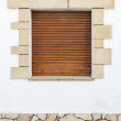Old white stone wall with brown wooden shutters — Stock Photo #55317343