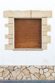 Old white stone wall with brown wooden shutters — Stock Photo