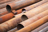 Rusted industrial steel pipes lay on the ground — Stock Photo