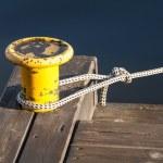 Yellow mooring bollard with nautical rope on pier — Stock Photo #55824381