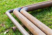 Bend of outdoor pipeline over green grass — Stock Photo