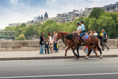 Mounted police riding past the bystanders on the bridge in Paris — Stock Photo